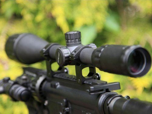 Sniper Scope in blurry green leaves background