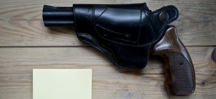Revolver gun in a black holster on top of a wooden table.